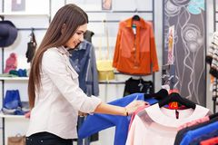 Beautiful woman shopping and looking at some clothing. Stock Photos