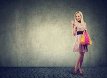 Beautiful woman shopping online checking prices on mobile phone. Fashion girl with colorful bags looking at cellphone Stock Photo