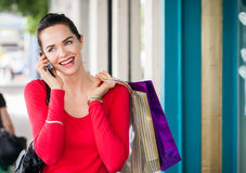 Beautiful woman shopping. A beautiful woman out shopping is talking on her mobile phone stock photo