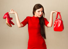 Beautiful woman after shopping. Beautiful woman in red dress holding high heel shoes and handbag Royalty Free Stock Photography