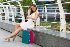 Beautiful woman shopping in the summer city. Stylish woman with paper bags shopping in the summer city Royalty Free Stock Photos