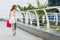 Beautiful woman shopping in the summer city. Stylish woman with paper bags shopping in the summer city Royalty Free Stock Photography