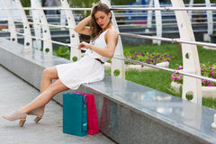 Beautiful woman shopping in the summer city. Stylish woman with paper bags shopping in the summer city Stock Photography