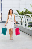 Beautiful woman shopping in the summer city. Stylish woman with paper bags shopping in the summer city Stock Images