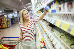 Beautiful woman shopping in supermarket. And deciding what to buy Stock Photos