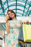 Beautiful woman in shopping using a mobile phone Royalty Free Stock Photos