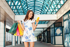 Beautiful woman in shopping using a mobile phone Royalty Free Stock Photo