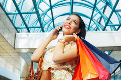 Beautiful woman in shopping using a mobile phone Royalty Free Stock Image
