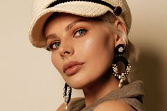 Beautiful woman with short blond hair in elegant clothes with accessories posing in studio. Fashion photo of beautiful woman with short blond hair in elegant royalty free stock image