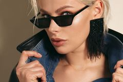 Beautiful woman with short blond hair in elegant clothes with fashion sunglasses. Fashion photo of beautiful woman with short blond hair in elegant clothes with stock photos