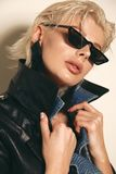Beautiful woman with short blond hair in elegant clothes with fashion sunglasses. Fashion photo of beautiful woman with short blond hair in elegant clothes with royalty free stock images