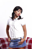 Beautiful woman short blue denim skirt white top. Stands in front of red sofa, white background Royalty Free Stock Image