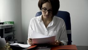 Beautiful woman with short, dark hair in glasses arranging documents from red folder on white office wall background royalty free stock photos
