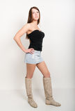 Beautiful woman in a short denim skirt, short top and boots Stock Photography
