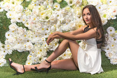 Beautiful woman in the short dress in front of the flowers backg Royalty Free Stock Photos