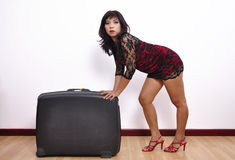 Beautiful woman short dress and high heels pushes suitcase Royalty Free Stock Images