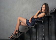 Beautiful woman in a short dress lying in chains Stock Photo