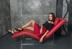 Beautiful woman in a short dress lying on the sofa Stock Photos