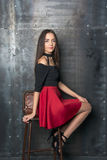 Beautiful woman in a short dress sits on a chair beside the wall Royalty Free Stock Image