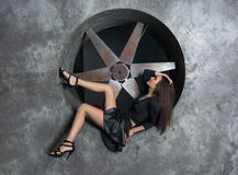 Beautiful woman in a short dress beside ventilation system at wa Stock Photography