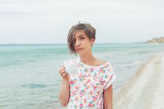 Beautiful woman relax during exotic vacation on the beach enjoying sweet coffee. Beautiful woman with short haircut relax during exotic vacation on the beach stock photo