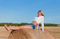 Beautiful woman in  short  posing on a wheat bale Royalty Free Stock Photos