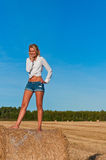 Beautiful woman in  short  posing on a wheat bale Stock Images