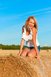 Beautiful woman in  short  posing on a wheat bale Royalty Free Stock Images