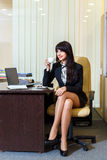Beautiful woman in a short skirt drinking coffee in  office Stock Image