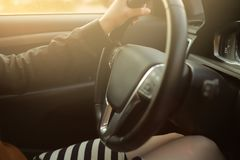 A beautiful woman in short skirt enjoys driving a luxury car in bright sunny light. Interior of a modern car driven by a beautiful woman in short striped skirt stock photography