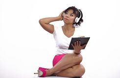 Beautiful woman short skirt uses tablet and headphone Stock Images