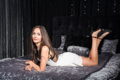 Beautiful woman in the short white dress on the bed Royalty Free Stock Photography