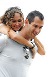 Beautiful woman on shoulders of smiling handsome m. Beautiful curly haired smiling woman with arms wrapped around the shoulders of happy handsome man both Stock Photography