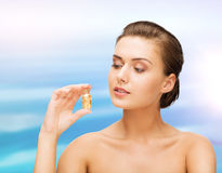 Beautiful woman showing bottle with golden dust Stock Photography