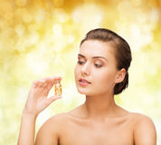 Beautiful woman showing bottle with golden dust Royalty Free Stock Image