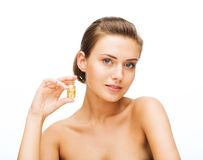 Beautiful woman showing bottle with golden dust Royalty Free Stock Photo