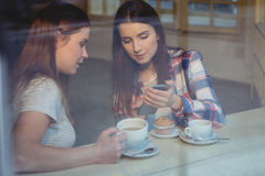 Beautiful woman showing cellphone to friend at cafe Stock Photography