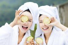 Beautiful woman showing fresh lemon in spa Royalty Free Stock Photo