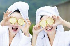 Beautiful woman showing fresh lemon in spa Stock Images