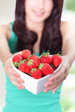 Beautiful woman showing fresh strawberries Stock Photography