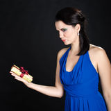 Beautiful woman showing a golden gift box Royalty Free Stock Images
