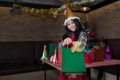 Beautiful woman showing green gift bag on hand in restaurant. concept of Christmas party and New year party. stock photos