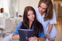 Beautiful woman showing hairstylist on a tablet examples hairsty Royalty Free Stock Photos
