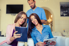 Beautiful woman showing hairstylist on a tablet examples hairsty Stock Photos