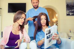 Beautiful woman showing hairstylist on a tablet examples hairsty Royalty Free Stock Images