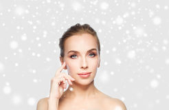 Beautiful woman showing her cheekbone over snow Royalty Free Stock Images