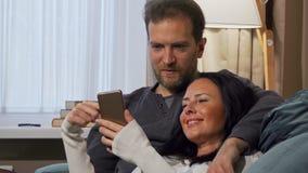 Beautiful woman showing her husband something funny on her smart phone. Beautiful women showing her husband something funny on her smart phone. Happy mature stock image