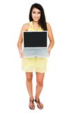 Beautiful woman showing laptop. Beautiful woman showing a laptop and posing isolated over white Royalty Free Stock Photo
