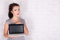 Beautiful woman showing laptop with blank screen over white bric Royalty Free Stock Photography