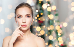 Beautiful woman showing lips over christmas lights. Beauty, people, holidays and plastic surgery concept - beautiful young woman showing her lips over christmas Royalty Free Stock Photos